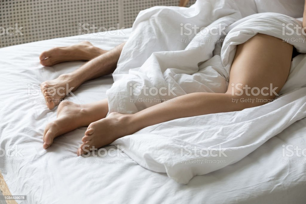Couple lying under white sheets in bed, lovers relaxing in cozy...
