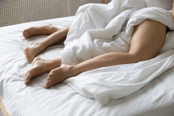 화이트이 불 침대에서 편안한 아래 거짓말 한 쌍의 다리 - 벌거벗은 뉴스 사진 이미지