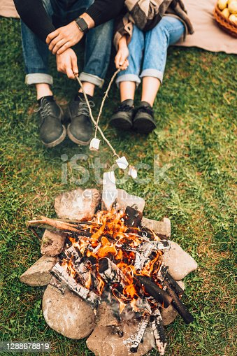 Legs of couple near fire who are roasting marshmallows. Picnic concept
