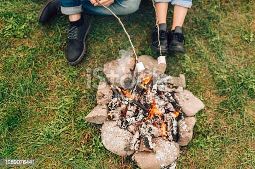 Legs of couple near fire who are roasting marshmallows. Picnic conceptLegs of couple near fire who are roasting marshmallows. Picnic concept
