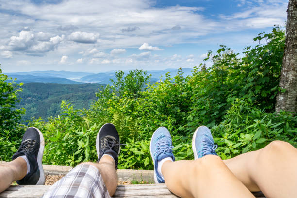 beine eines paares ruht auf schwarzwald-berg, die atemberaubende aussicht über naturlandschaft genießen - sommerferien baden württemberg stock-fotos und bilder