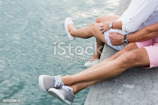 Cropped view of the legs of a mature couple sitting on a dock by the water, legs dangling over the edge.  They are wearing shorts and shoes.