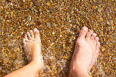 feet of dad and daughter stand ashore in the water