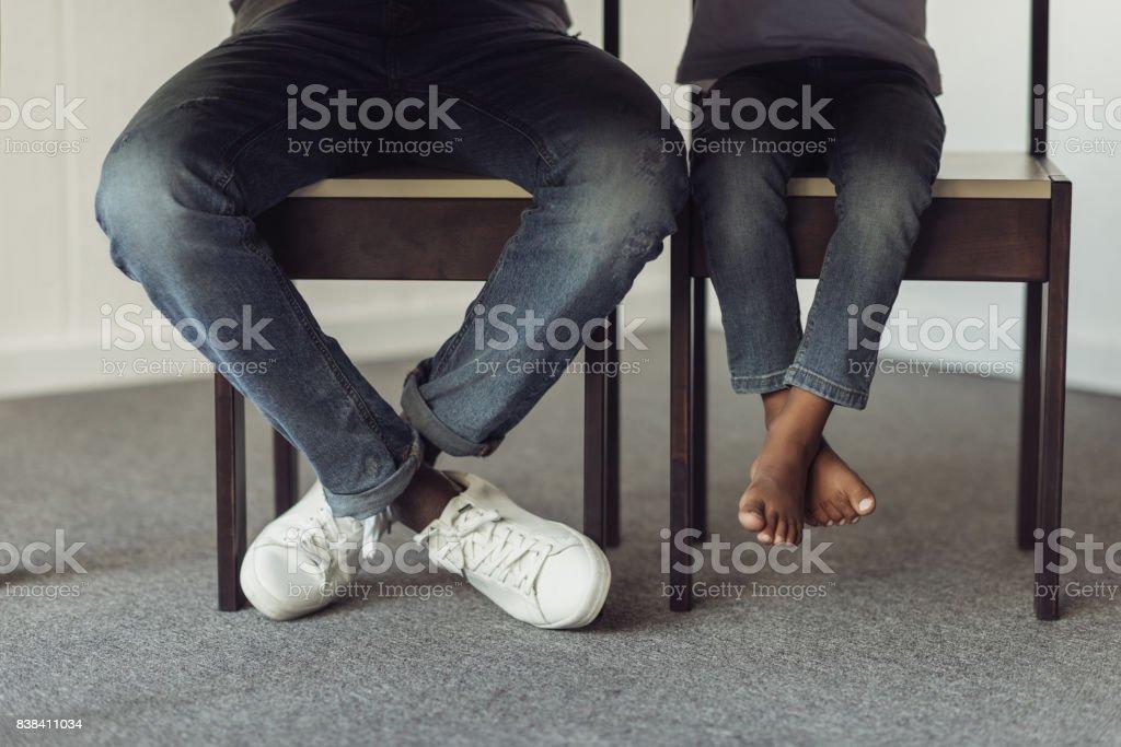 Beine von Vater und Sohn unter Tisch – Foto