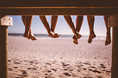Rearview cropped shot of a row of legs of friends sitting who are sitting in a row on a beach boardwalk with sand and sea in front of them