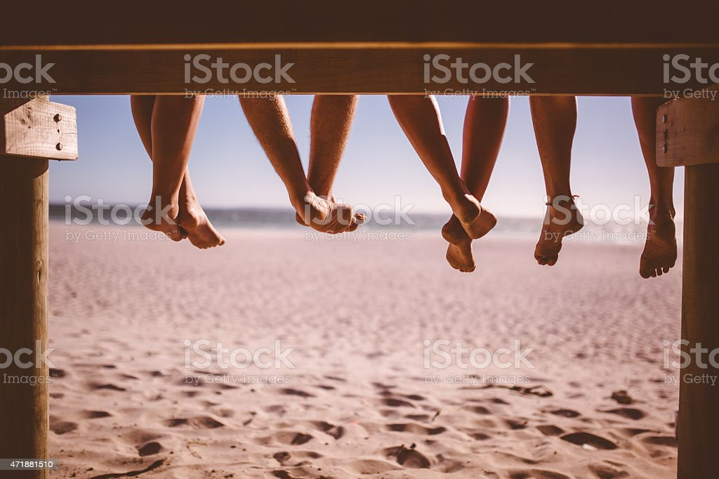 Legs of friends sitting on a beach boardwalk together stock photo
