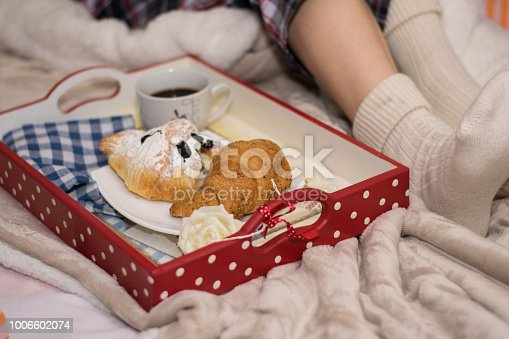 618750646 istock photo Legs of girl warm socks and breakfast in bed 1006602074
