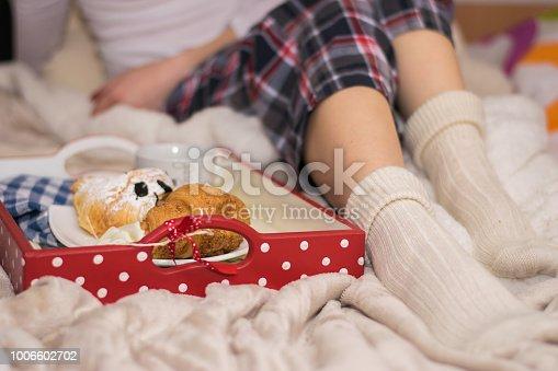618750646istockphoto Legs of girl warm socks and breakfast in bed 1006602702