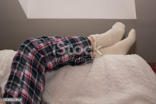 618750646 istock photo Legs of girl warm socks 1006602644