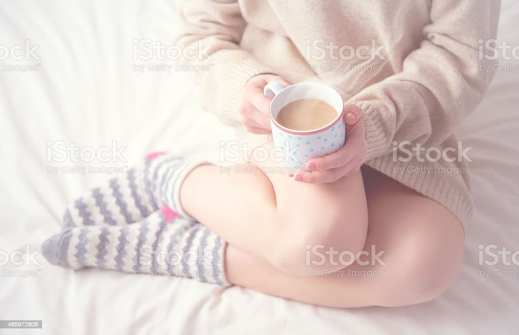 legs of girl warm woolen socks and  cup of coffee stock photo