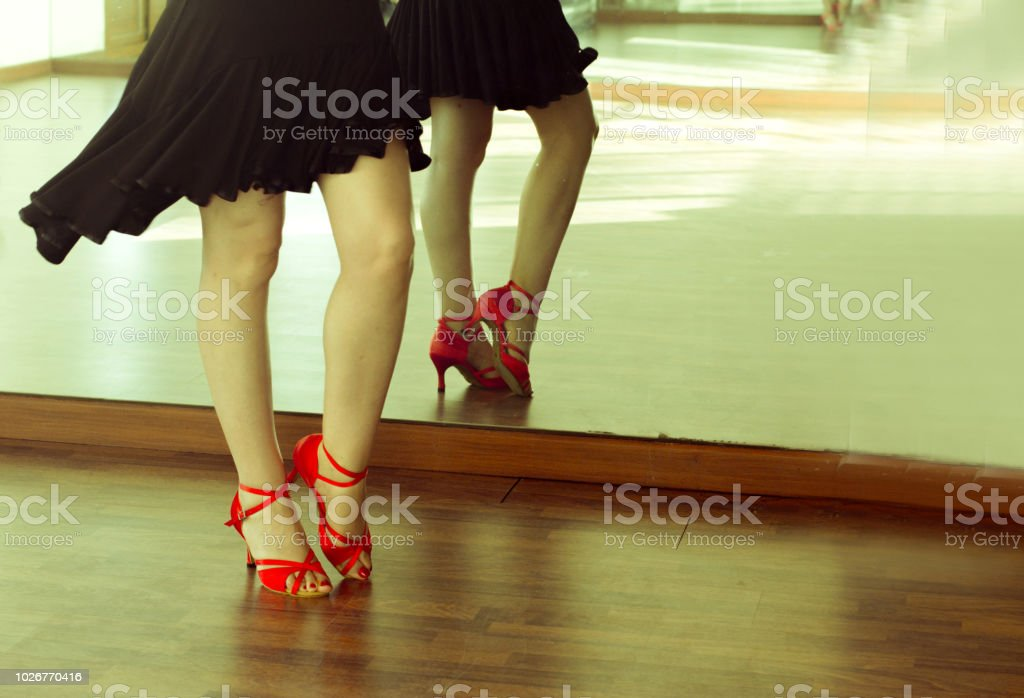 Legs of girl with red shoes dancing stock photo