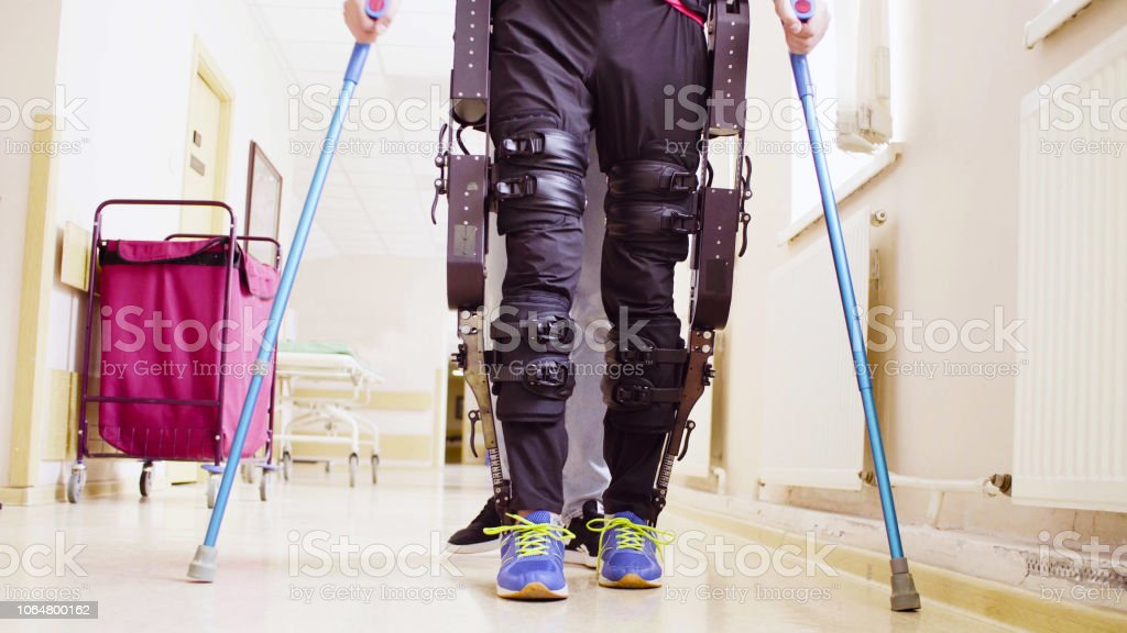 Legs of invalid in robotic exoskeleton walking through the corridor Legs of disable man in the robotic exoskeleton walking through the corridor of the rehabilitation clinic. Doctor helping him. Adult Stock Photo