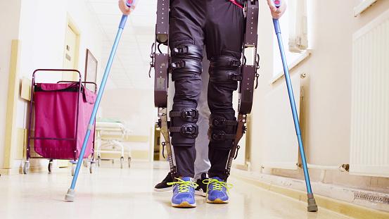 Legs Of Invalid In Robotic Exoskeleton Walking Through The Corridor Stock Photo - Download Image Now