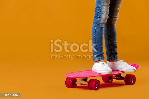 legs of little girl in white sneakers and jeans on pink skateboard on orange background