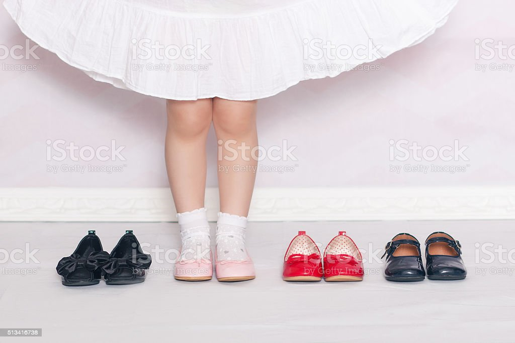 legs of little girl in white socks in pink shoes stock photo