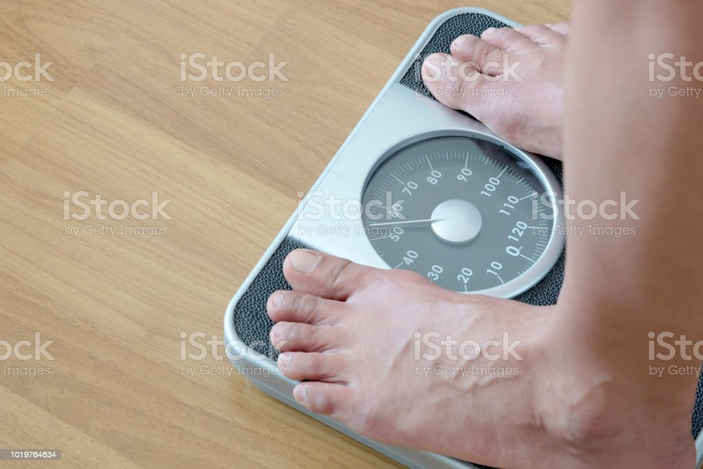Legs of men standing on scales weight. Concept of health and weight loss. stock photo