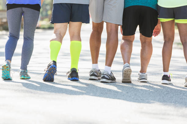 legs of people in sports clothing walking away - old man feet stock photos and pictures