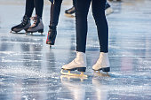 legs of boys and girls skating on winter day closeup