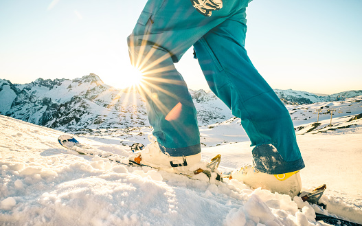 Legs of professional skier at sunset on relax moment in french alps ski resort - Winter sport concept with adventure guy on mountain top ready to ride down - Side view point with azure vintage filter