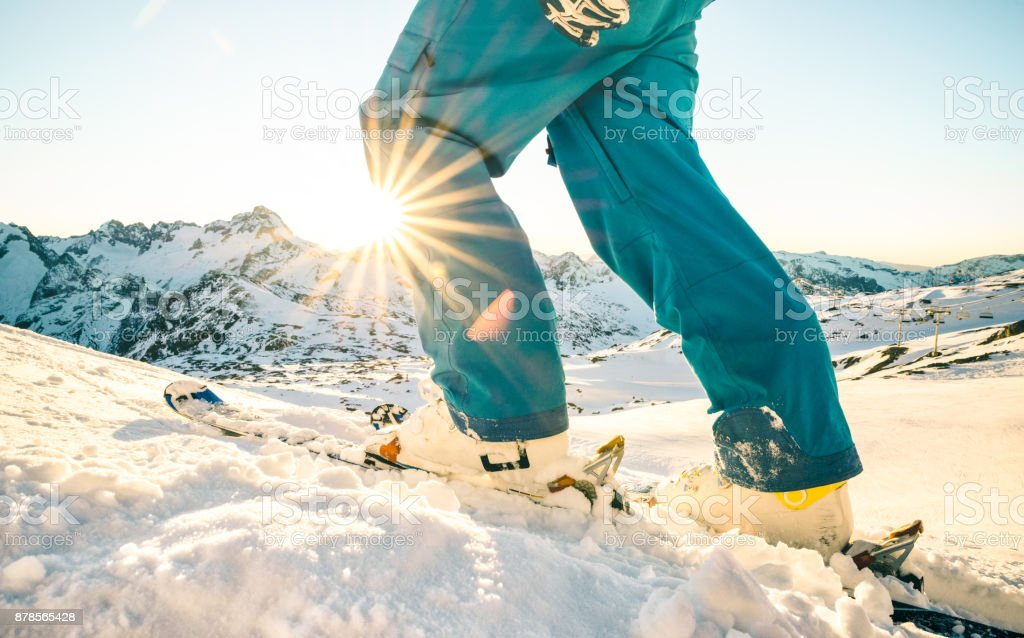 Legs of professional skier at sunset on relax moment in french alps ski resort - Winter sport concept with adventure guy on mountain top ready to ride down - Side view point with azure vintage filter stock photo