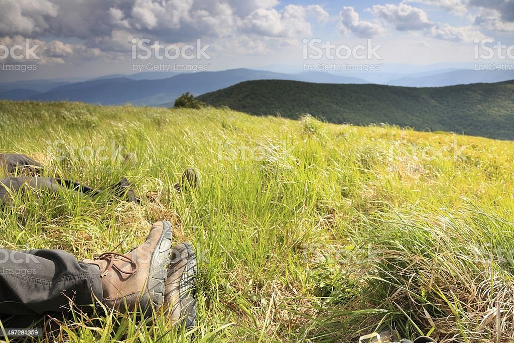 Legs of resting tourist in the mountain landscape. stock photo