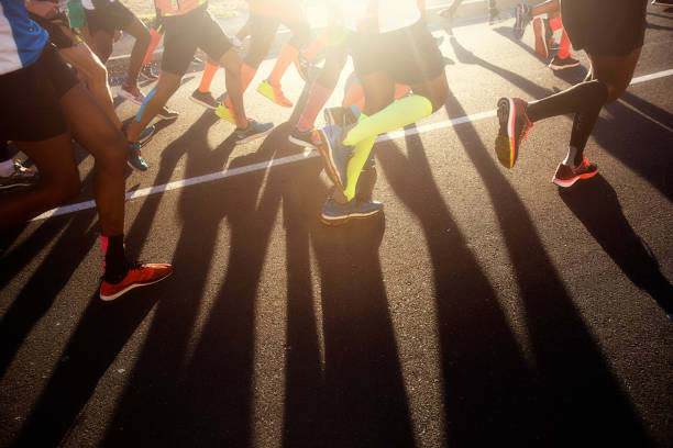 legs of road runners with shadow on rod - marathon stock photos and pictures