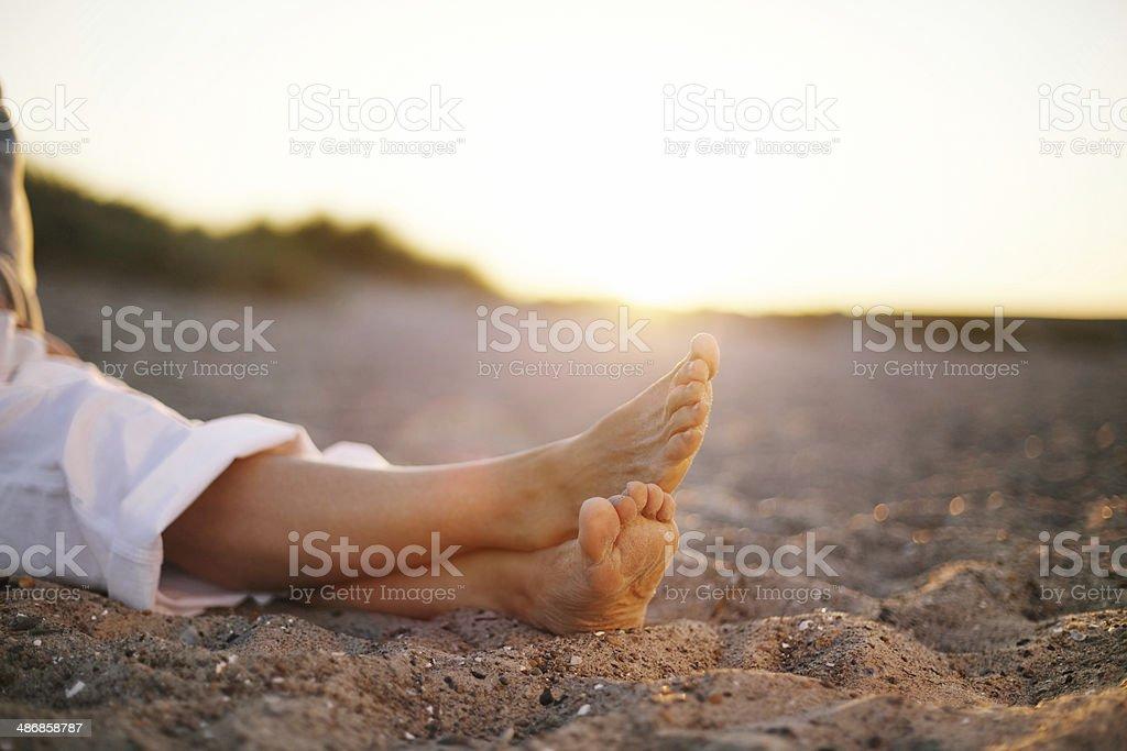 Legs of senior woman sitting on beach stock photo