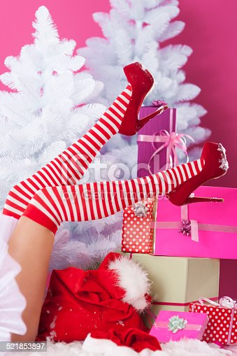 istock Legs of sexy santa claus with christmas presents 521853897