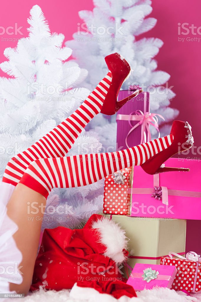 Legs of sexy santa claus with christmas presents stock photo