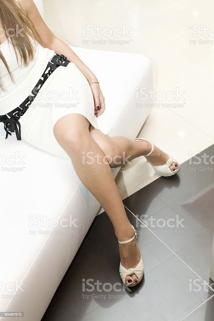 Legs of sexy woman sitting on sofa stock photo