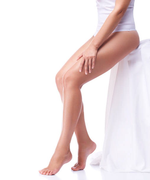 Legs of slim tanned girl isolated on white background stock photo
