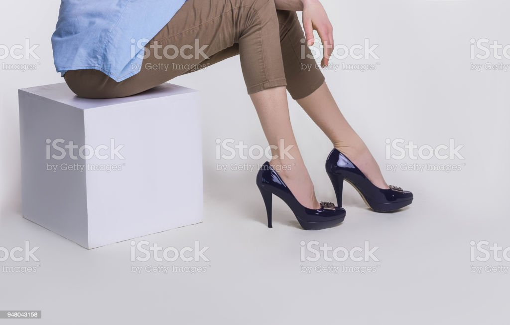 Legs of slim young woman in stylish high-heeled shoes sitting on white background stock photo