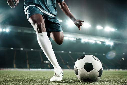 Legs of african soccer player kicking the ball at stadium