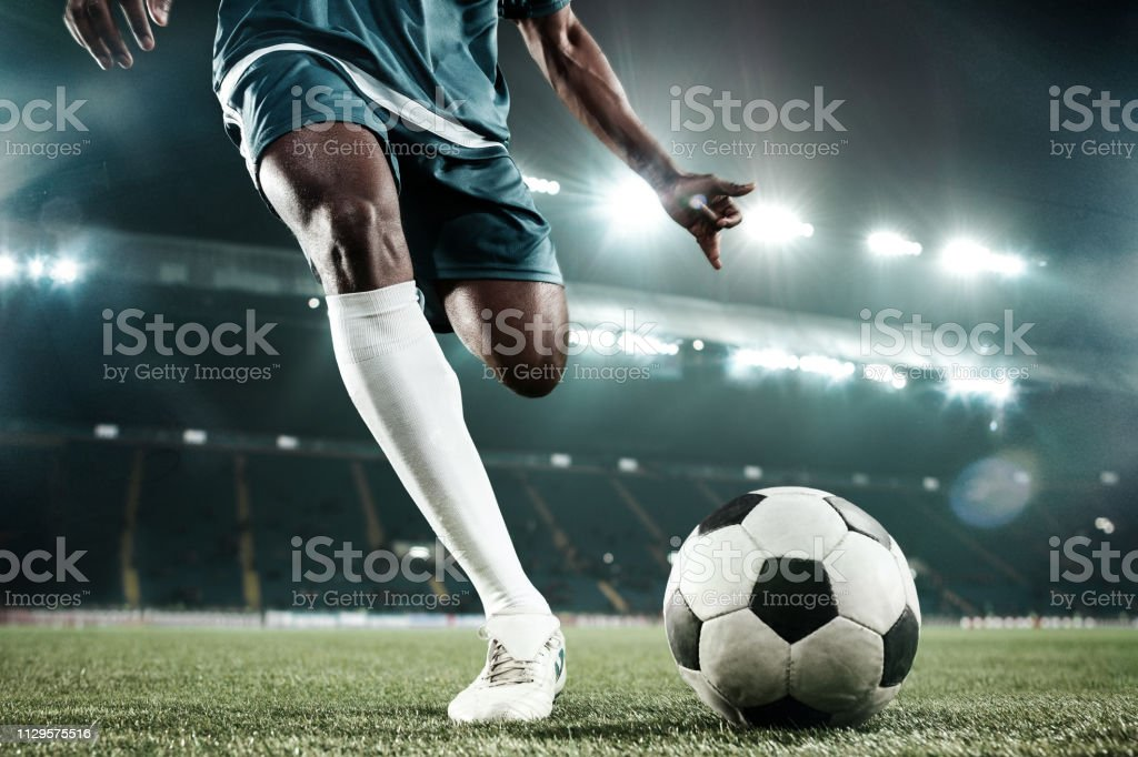 Legs of soccer player kicking the ball stock photo