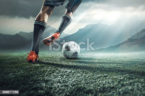 istock Legs of soccer player kicking the ball 698677286