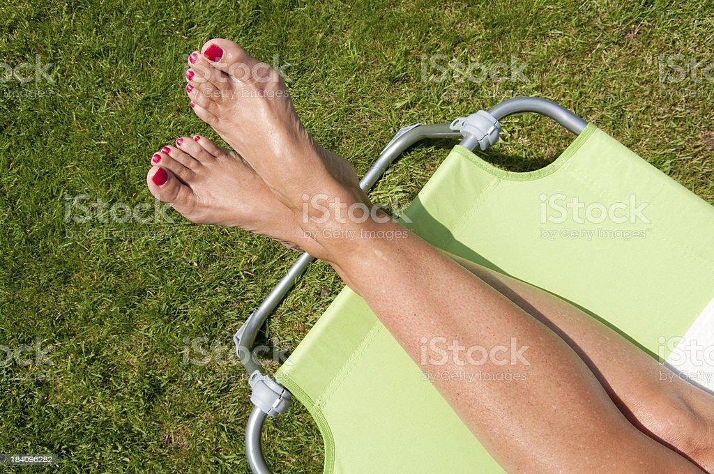 Gambe Di Donna Prendere Il Sole In Giardino Su Sunlounger