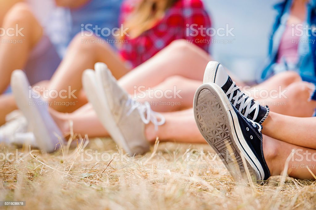 Legs of teenagers, canvas shoes, summer music festival stock photo