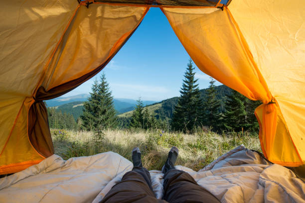 legs of the traveler in an camping tent outdoors stock photo