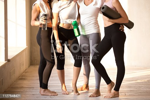 Legs of toned diverse girls standing together hugging after training in fitness studio, fit young females wearing sport leggings relax holding water bottle and yoga mat, embracing after workout