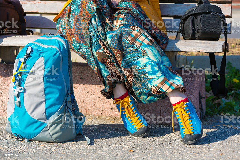 Legs of Tourist resting wooden bench park backpack camera bag stock photo
