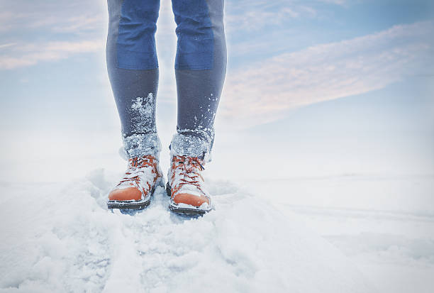 Legs of traveler standing in snow outdoor. Travel and discovery stock photo