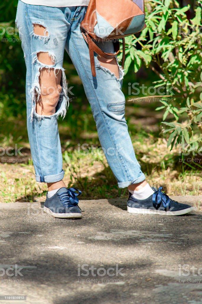 Piernas De Mujer En Pantalones De Mezclilla Rotos Y Zapatillas Con Bolsa Sobre Fondo De Arboles En El Parque Foto De Stock Y Mas Banco De Imagenes De A La Moda