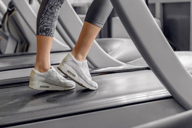 legs of woman running on treadmill - runner rehab gym foto e immagini stock