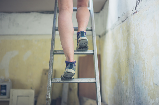 The legs of a young woman standing on a ladder to the loft