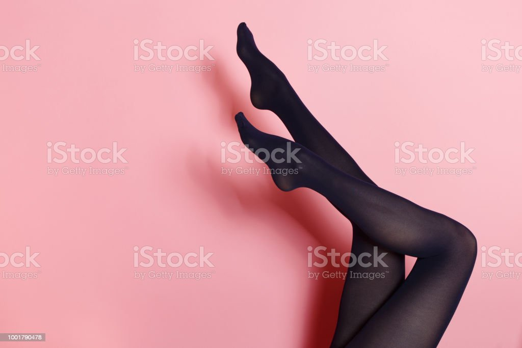 Legs of young caucasian woman in black tights stock photo