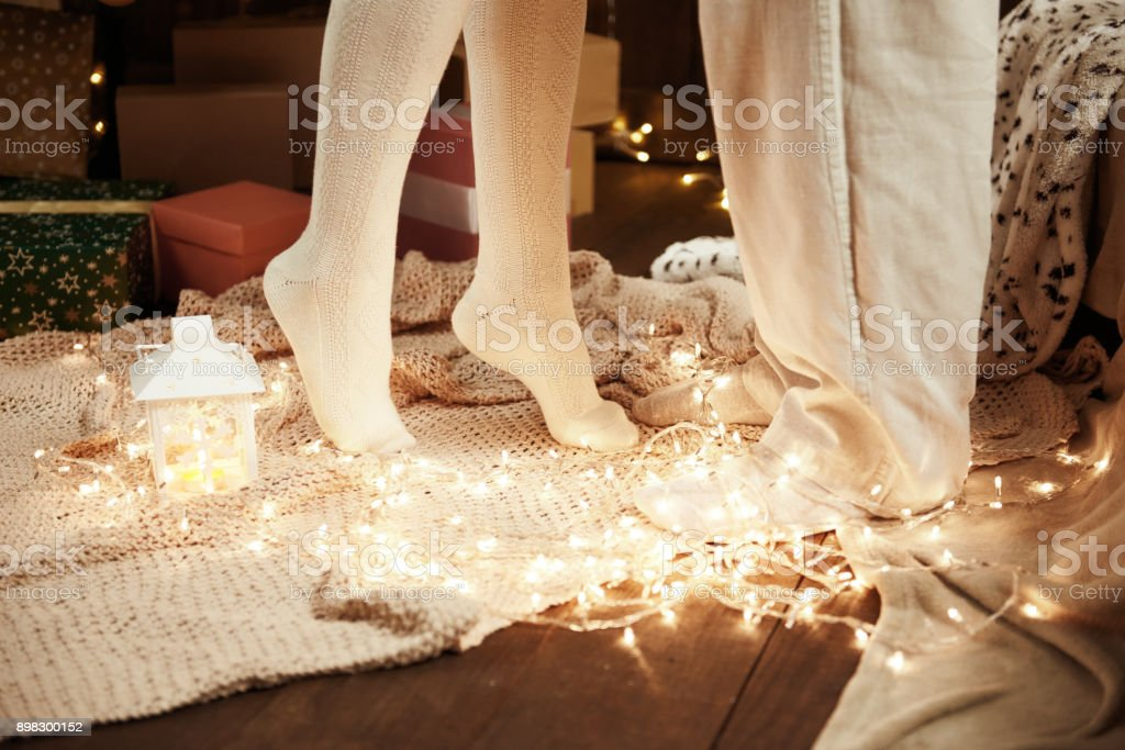Legs of young couple in dark wooden interior with lights, candle lantern. Man and woman hugging. New year holiday. Christmas lights and decoration. Dressed in white. Romantic evening. stock photo