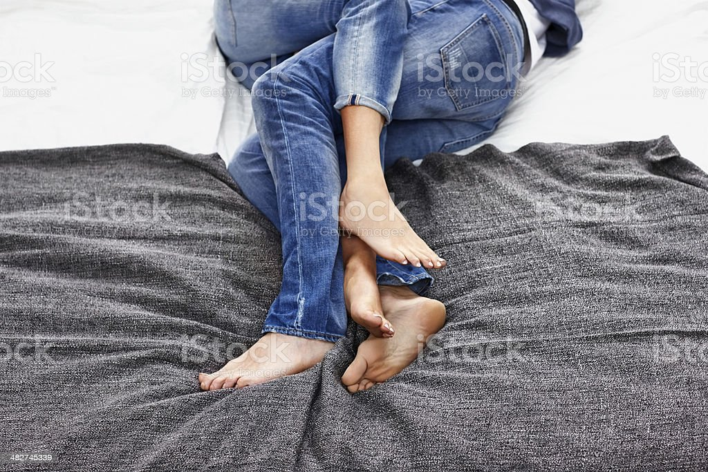 Legs of young couple lying together on bed stock photo