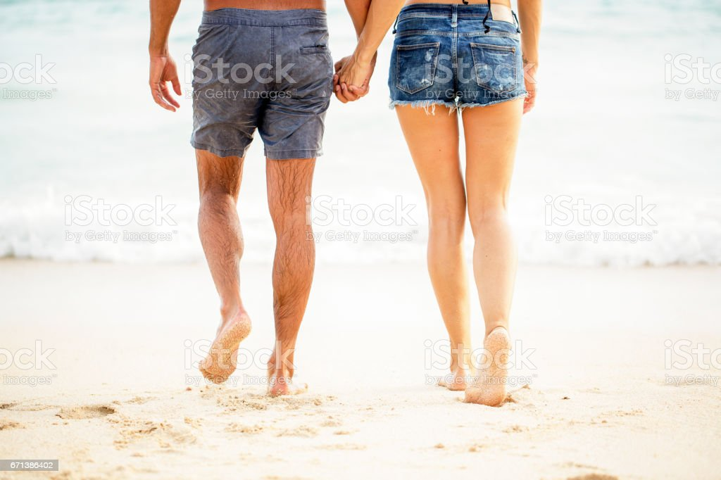 Legs of young couple walking on sand at seaside stock photo
