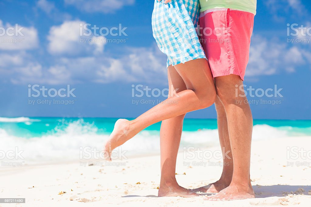legs of young hugging couple on tropical turquoise beach stock photo