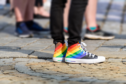 legs of young man in a sneakers with rainbow symbol of LGBT. LGBTQ+